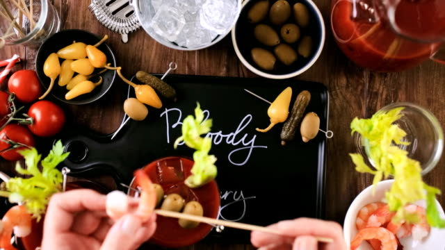 Preparing bloody mary cocktail with olives, pickles, and cocktail shrimp garnish. video