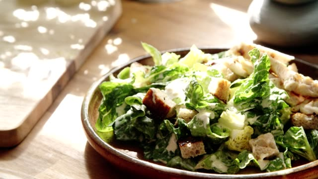 preparing cesar salad with chicken, lettuce and parmesan - insalata video stock e b–roll