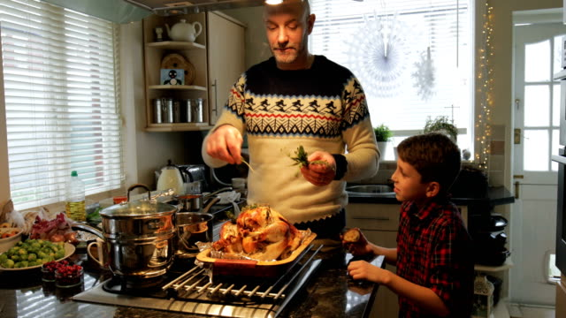 Preparing Christmas Dinner Mature man is preparing christmas dinner in the kitchen of his home. His son is talking to him and eating a mince pie. turkey stock videos & royalty-free footage