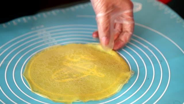 tatlı yumurta dilimleri mango sarma için hazırlanıyor - kek dilimi stok videoları ve detay görüntü çekimi