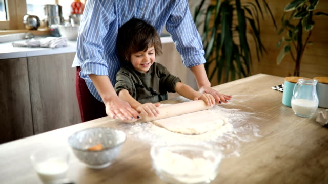 Preparing dough for biscuits Single mom and her son spending their time together in the kitchen making cookies flour stock videos & royalty-free footage