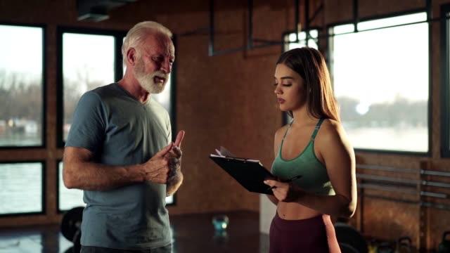 stockvideo's en b-roll-footage met samen een oefenplan voorbereiden - fitnessleraar