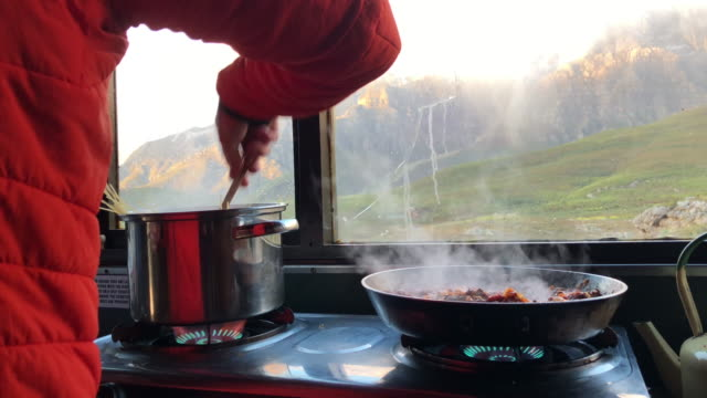 Preparing food in the mountain hut A male hiker with an orange jacket on prepares a warm dish of mince and pasta in the mountain hut western cape province stock videos & royalty-free footage