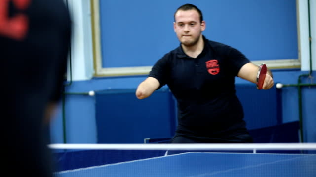 Preparing for paralympic games Young man with differing abilities,amputated arm, playing table tennis indoors with left hand disability stock videos & royalty-free footage