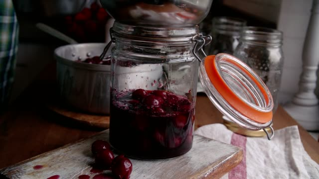 vídeos de stock e filmes b-roll de preparing homemade cooked cherries and canning in jars - jam jar
