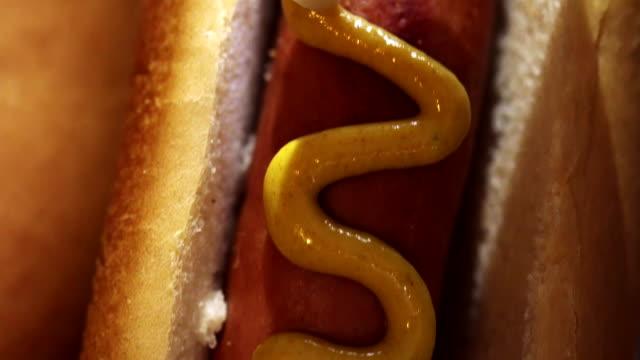 Preparing Hot Dog with Mustard and Ketchup video