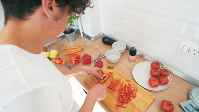 Preparing ingredients for a new recipe. Young man in the kitchen cutting peppers. He is cooking a vegetarian dish. ingredient stock videos & royalty-free footage