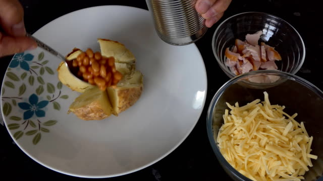 Preparing jacket potato Close up of hands preparing jacket potato, filling with baked beans, cooked meat and grated cheese for oven or convection microwave cooking stuffed stock videos & royalty-free footage