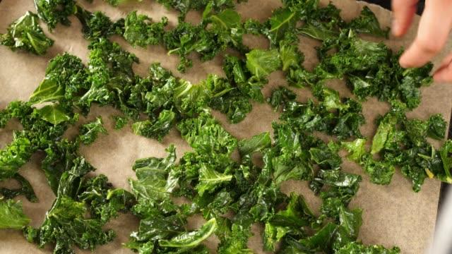 zubereitung von grünkohlchips auf tablett mit backpapierverlegung - grünkohl stock-videos und b-roll-filmmaterial