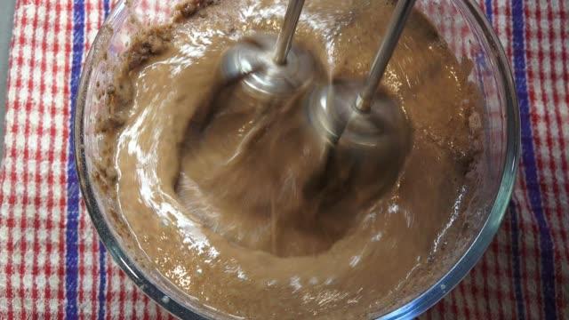 vidéos et rushes de préparation du chocolat de mousse avec le mélangeur de main au-dessus de la vue - batteur électrique