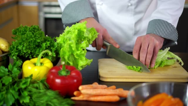 preparing salad - chef cutting lettuce on board in kitchen video