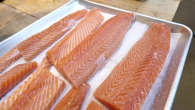 Preparing Salmon fillet for refrigeration A chef preparing Salmon fillet in a pan for refrigeration. A handsome cook placing salmon fillet into pan for further refigiration. Anthelmintic seafood freeze. Raw seafood. Closeup fillet stock videos & royalty-free footage