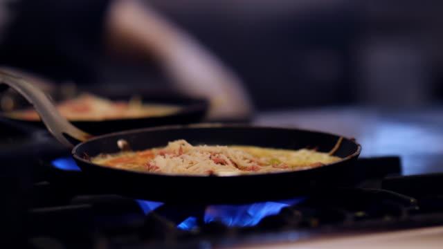 Preparing scrambled eggs in black frying pan on cooker.