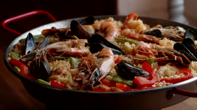 preparing seafood paella with shrimps, squid, mussels, green beans and paprika - seafood stock videos and b-roll footage