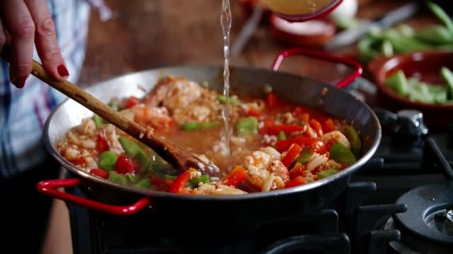 preparing seafood paella with shrimps, squid, mussels, green beans and paprika - spanish food stock videos and b-roll footage