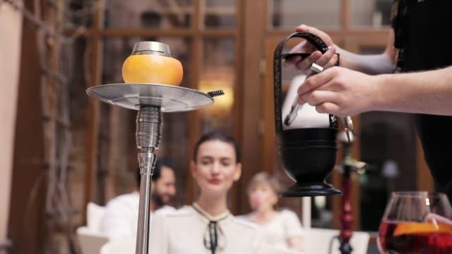 vídeos de stock e filmes b-roll de preparing shisha. man hands putting charcoal into hookah bowl - saladeira