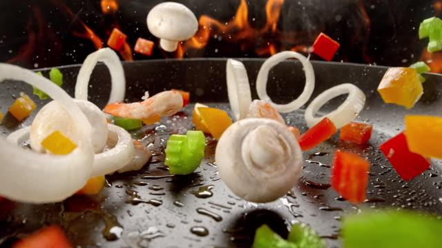 preparing stir-fried asian food in burning frying pan - sedano video stock e b–roll