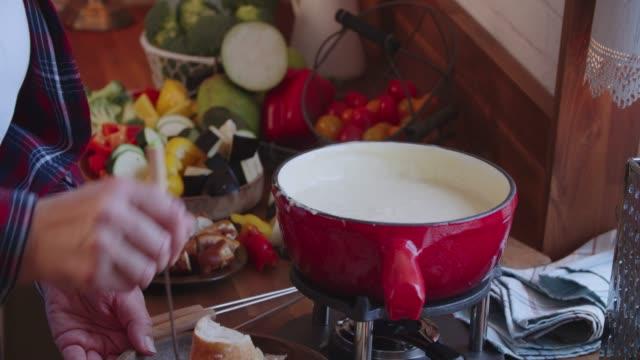 preparare la fonduta di formaggio svizzero in una pentola servita con pane - immergere video stock e b–roll
