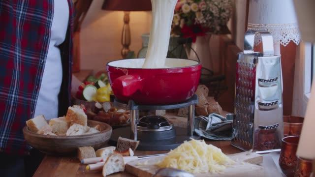 パンと一緒に鍋でスイスのチーズフォンデュを準備 - チーズ 溶ける点の映像素材/bロール
