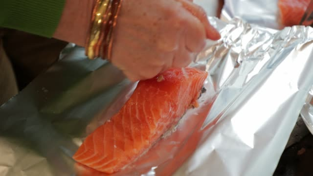 Preparing The Salmon A woman is preparing to cook salmon in tin foil fillet stock videos & royalty-free footage