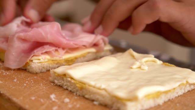 vídeos de stock e filmes b-roll de preparing the sandwiches, adding the ingredients-close up - sanduíche