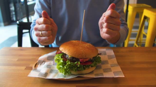 vídeos de stock, filmes e b-roll de preparando-se para comer hambúrguer - hamburguer
