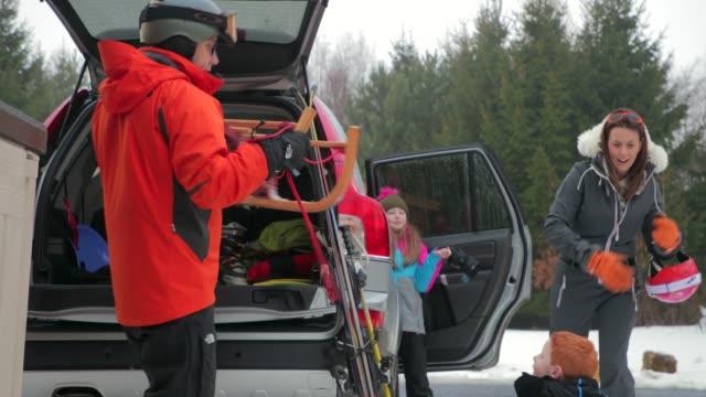 preparing to ski with his family - sprzęt sportowy filmów i materiałów b-roll