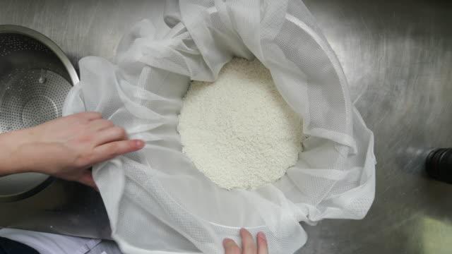 布が付いているボールの中に米を入れて準備の伝統的なアジアの米 - 洗う点の映像素材/bロール