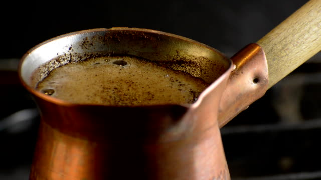 Preparing turkish coffee in copper cezve on gas stove. video