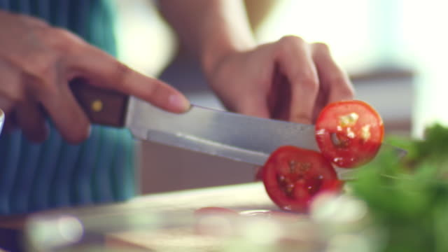 vídeos de stock e filmes b-roll de preparing vegetable : cutting tomato - vegetables