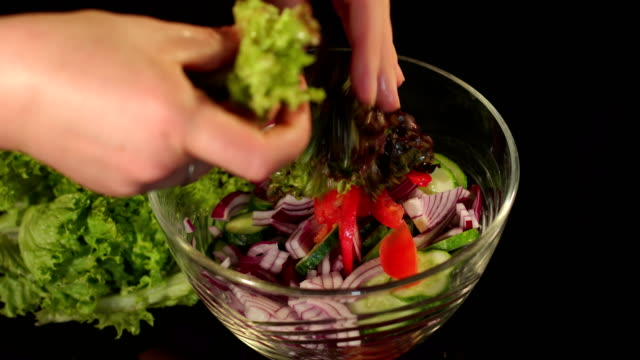 Preparing vegetable salad with lettuce, close-up. video