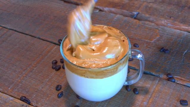 zubereitung whipped dalgona kaffee auf einem holztisch. - milchkaffee stock-videos und b-roll-filmmaterial