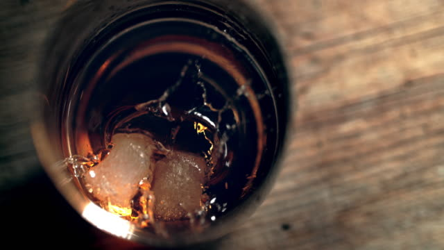 slo mo preparing whisky on the rocks - bancone bar video stock e b–roll