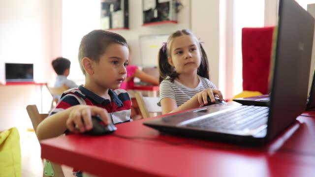 vidéos et rushes de garçon et fille préscolaires utilisant des ordinateurs portatifs dans l'école privée d'it - enfant d'âge pré scolaire
