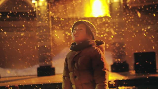 Preschool boy playing in the snow at night.