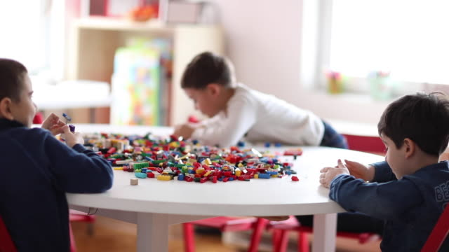 Preschool boys playing with plastic blocks at playroom of private school Preschool boys playing with plastic blocks at playroom of private school playroom stock videos & royalty-free footage