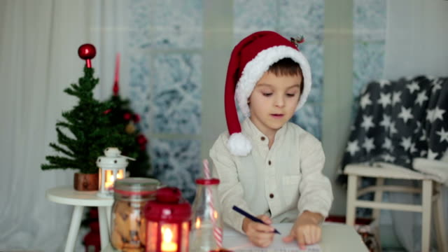 Preschool child, boy, writing letter to Santa at home, while snowing outdoors, eating cookies video