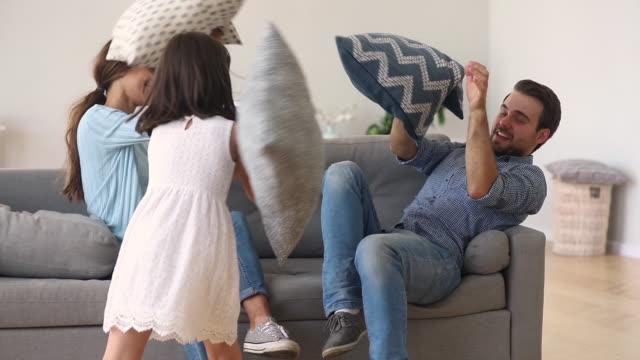 stockvideo's en b-roll-footage met preschool dochter spelen met kussengevecht met actieve ouders - couple fighting home