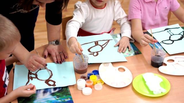 vídeos y material grabado en eventos de stock de educación preescolar - niños de kinder pintan colores de pájaros de invierno - cuidado infantil