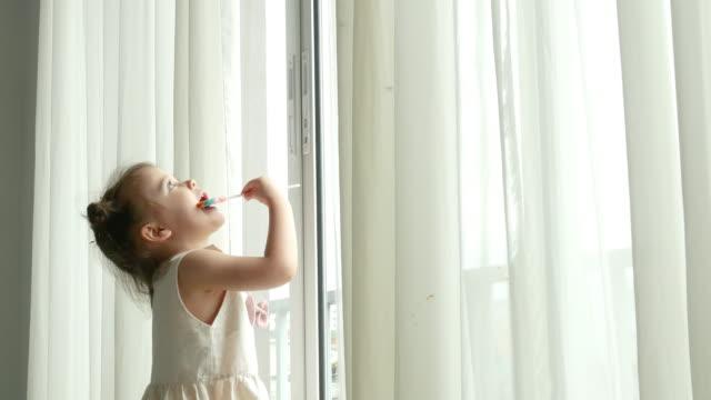 Preschool girl eating lollipop , homeschooling concept