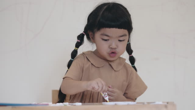 Preschool girl squeezing yellow watercolor paint tube