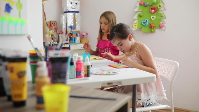 ragazze in età prescolare che dipingeno con i colori dell'acqua in classe - arti e mestieri video stock e b–roll