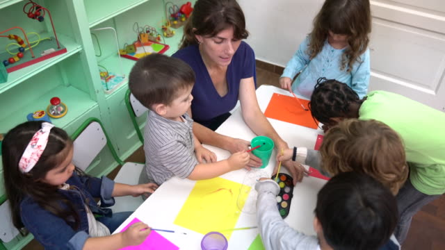 Preschool kids painting with teacher at classroom High angle view of teacher sitting amidst students coloring in classroom. Preschool kids are painting at desk in kindergarten. They are in school building. child care stock videos & royalty-free footage
