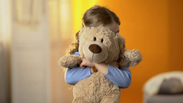 Preschool shy girl hiding behind teddy bear, childish psychological problems Preschool shy girl hiding behind teddy bear, childish psychological problems autism stock videos & royalty-free footage
