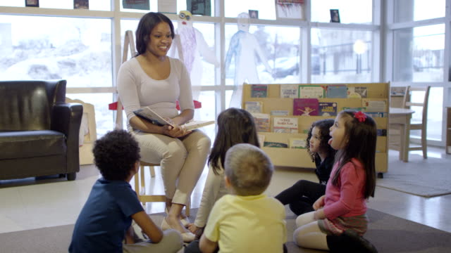 Preschool Story Time A multi-ethnic group of preschool children sitting on the floor listening to the teacher / babysitter read a story. child care stock videos & royalty-free footage