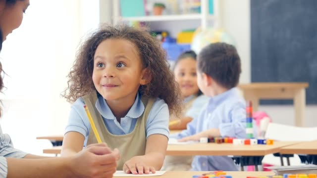 Preschool teacher helps cute mixed race schoolgirl in class video