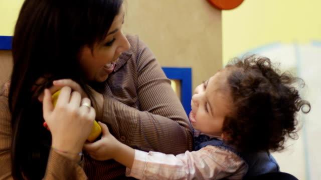 vídeos y material grabado en eventos de stock de parvulario, maestro jugando y riendo con niña bebé - escuela preescolar