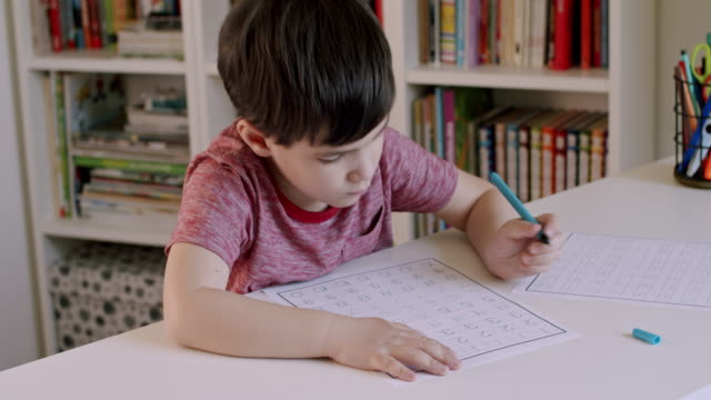 Preschooler boy learning to write numbers.