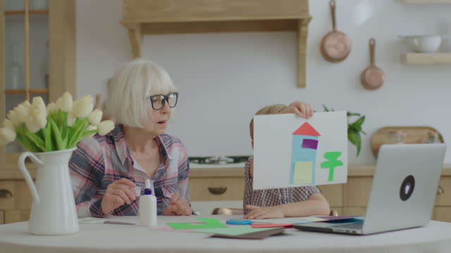 Preschooler makes art homework with glue, scissors and color paper and shows his artwork to laptop. Senior grandmother helping kid with applique. Family making arts together. Online education process.