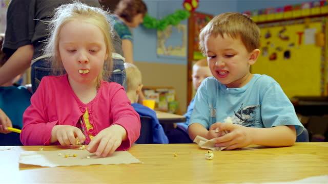 stockvideo's en b-roll-footage met preschoolers clean up their snacks - peuterklasleeftijd